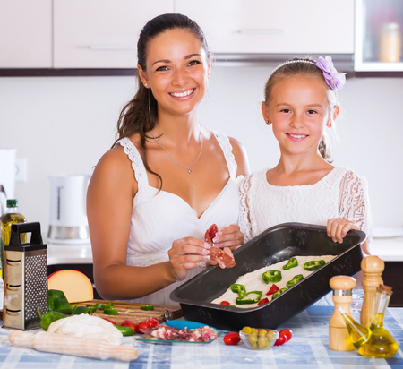 25s: Smiling family of two making pizza with vegetables and bacon