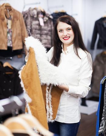 ordinary woman: Ordinary woman choosing jacket at fashion boutique
