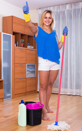 ordinary woman: Smiling adult girl washing floors at home using liquid detergent