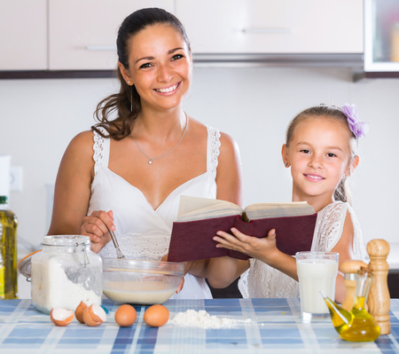 teaching adult: adult american housewife teaching daughter to prepare omelette and smiling