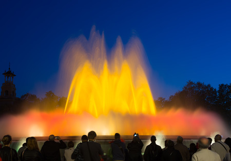 gazer: BARCELONA, SPAIN - APRIL 17, 2015: Evening view at colorful  fountain Montjuic show and people watching it nearby in Barcelona.  Catalonia
