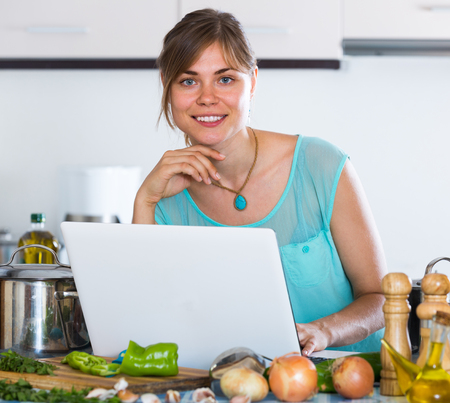 householder: Happy housewife cooking vegetables basing on new recipe in interior