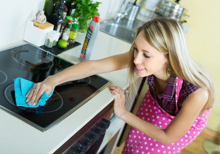 tidying up: Smiling young woman tidying up kitchen-range after cooking