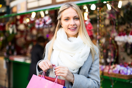 charmingly: Beautiful blonde smiling charmingly at a Christmas market.Fair lights are visible at distance
