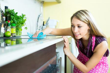 gospodarstwo domowe: Atrakcyjna kobieta czyszczenia mebli w kuchni z szmatę Zdjęcie Seryjne