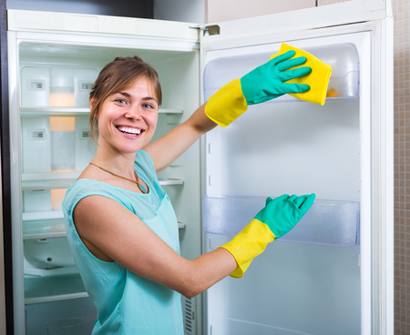 handglove: Cheerful smiling girl wiping fridge parts with lint-free rag Stock Photo