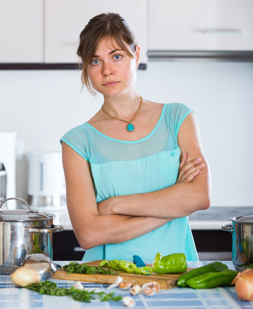 unwillingness: Portrait of tired young woman at home kitchen