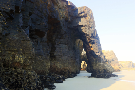 falling tide: Natural arch at  sand  beach in  day time. Atlantic Ocean coast of Spain Stock Photo