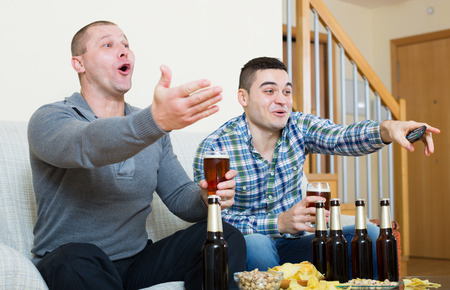fandom: Adult friends sitting at table with beer and commenting sport tv channel in apartment Stock Photo