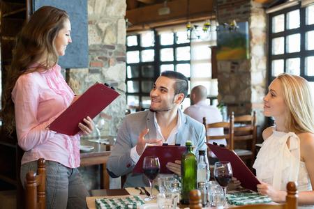 respectful: Portrait of cheerful people having dinner and respectful waiter Stock Photo
