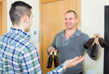 buddy: Guy meeting smiling buddy with beer bottles  indoor