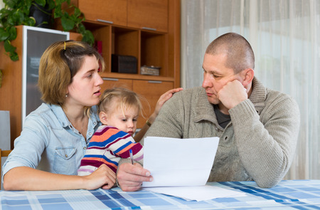 needs: Worried family with child sitting with financial documents at home