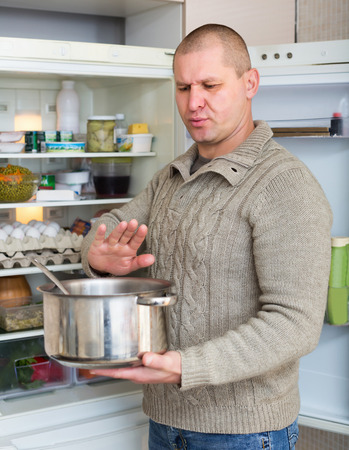 foul: Man holding foul food near refrigerator at kitchen