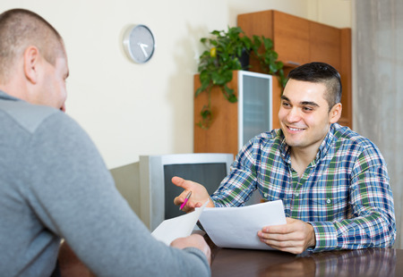 financial advice: Adult smiling man helping friend to fill banking document at home