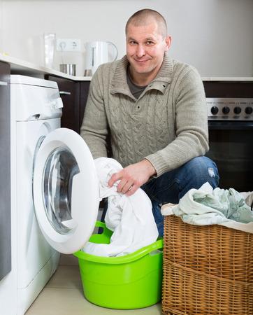 man laundry: Home laundry. Ordinary smiling man using washing machine at home