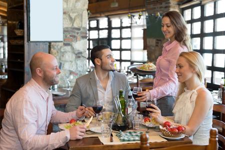 Grupo de gente feliz con la cena en el restaurante rural y beber vino. Concéntrese en el joven Foto de archivo