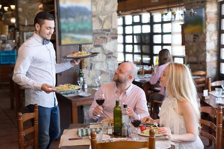 Couple de manger délicieux et salades fraîches dans un restaurant tout serveur leur apporte de la nourriture plus végétarienne