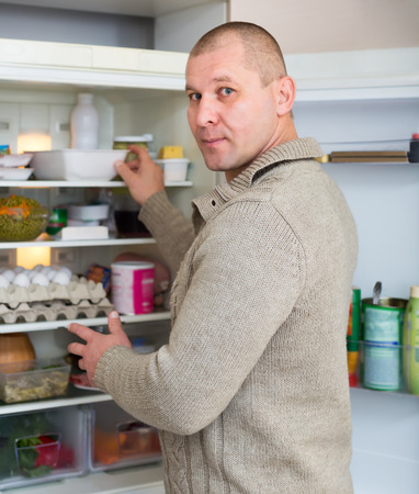 refrigerator kitchen: Hungry man in the kitchen is searching for food in the refrigerator