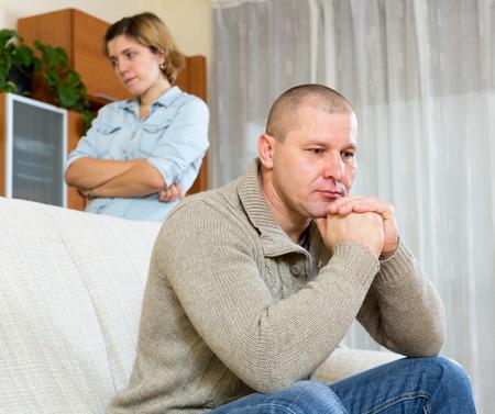 divorcio: Pelea de la familia. Hombre de la tristeza y el llanto contra la mujer joven en su casa