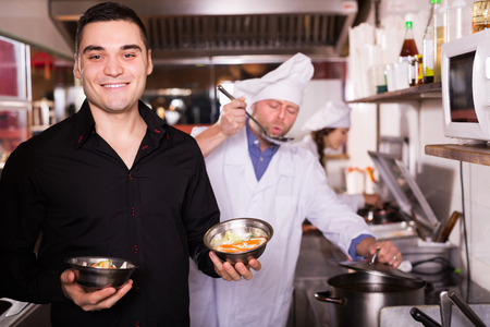 house robes: Chefs and smiling waiter working at eating house
