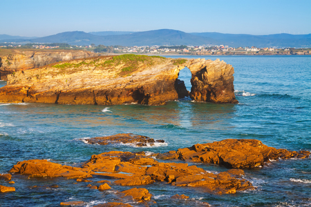influx: Natural arch at As Catedrais beach in flowing sea. Atlantic Ocean coast of Spain Stock Photo