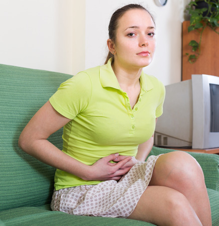 disordered: Young female suffering of disordered stomach holding hands on belly