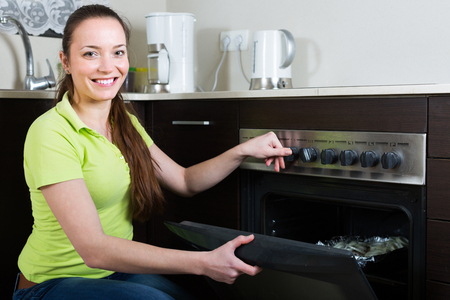 cook house: Happy woman cooking food in oven at home kitchen Stock Photo