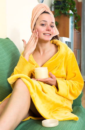 house robe: Woman after shower wearing a bathrobe sitting on a sofa and using lotion to moisturize skin on her face