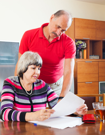 calculated: serious mature woman with husband reading financial documents at table in home interior Stock Photo