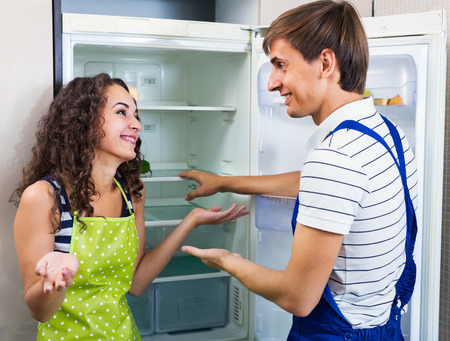 fridge: Satisfied housewife grateful to serviceman for help with fridge