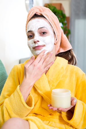 house robe: Portrait of a woman in a bathrobe in livingroom with a face mask on her face