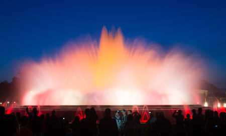 gazer: BARCELONA, SPAIN - APRIL 17, 2015: Evening view at colorful vocal fountain Montjuic show and people watching it nearby in Catalonia.