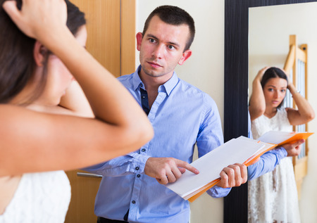 landlord: Portrait of confused tenant and furious landlord with a unpaid bills indoors Stock Photo