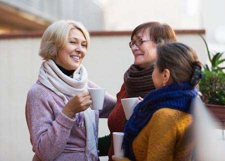 Ältere Frau in der warmen Kleidung mit Tasse heißen Tee auf der Terrasse