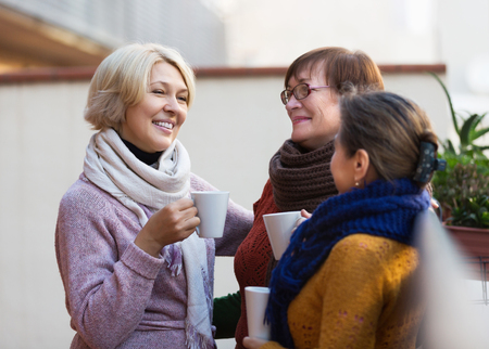 coffee meeting: Mature female in warm clothes having cup of hot tea on terrace