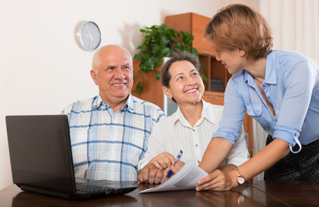 retirement: Mature couple answer questions of outreach worker with laptop in office