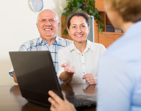 census: Smiling aged couple talking with employee with laptop at home. Focus on woman
