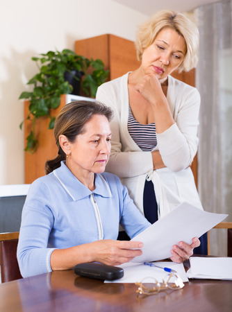 woman portrait: Upset female pensioners reading documents with sad faces at home. Focus on brunette