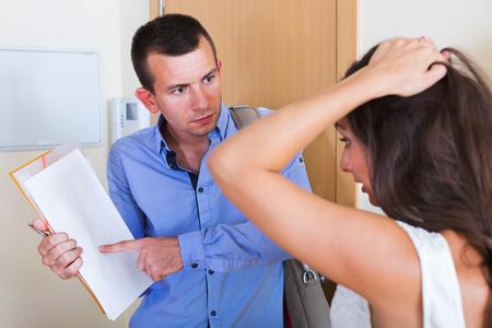 angry couple: Retrato de arrendatario y arrendador confusa furiosa con facturas pendientes de pago en el hogar
