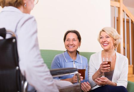 break from work: Smiling senior ladies visiting disabled friend indoor. Focus on brunette Stock Photo