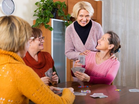 leisure game: Happy smiling aged female friends playing cards at home