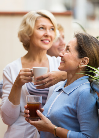 mature women: Three positive mature women drinking tea with cookies at balcony. Focus on brunette