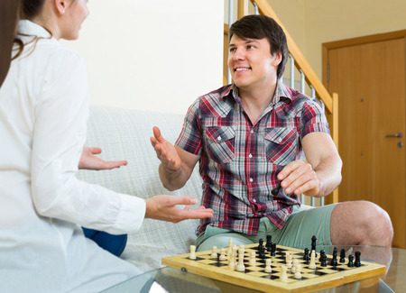 spanish home: Relaxed spanish couple playing chess at home sitting on the sofa