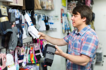 socks: Young man choosing socks at the shop and smiling