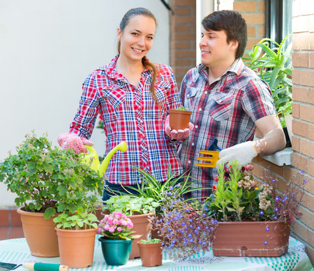 smiling woman in a greenhouse: Happy couple working with flowers at the balcony. Focus on girl