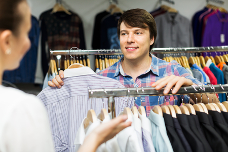 choosing clothes: Positive couple choosing clothes in commercial centre Stock Photo
