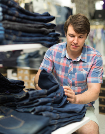 levis: Young guy choosing blue jeans at the shop