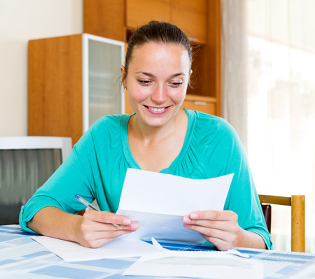 filling out: Cheerful girl filling out tax forms while sitting at her desk