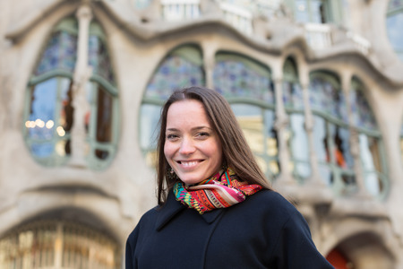 paseig: Portrait of female tourist with Casa Batllo  by Antoni Gaudi in background
