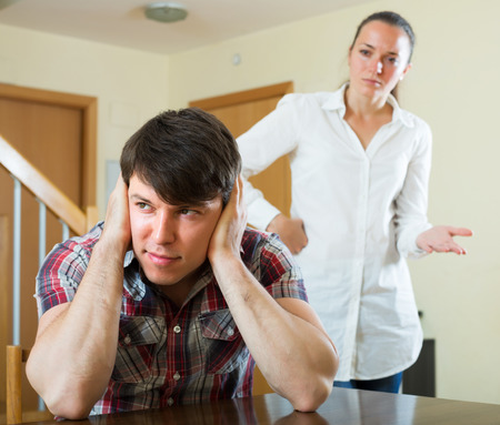 squabble: Unhappy guy and sad woman during conflict in living room at home